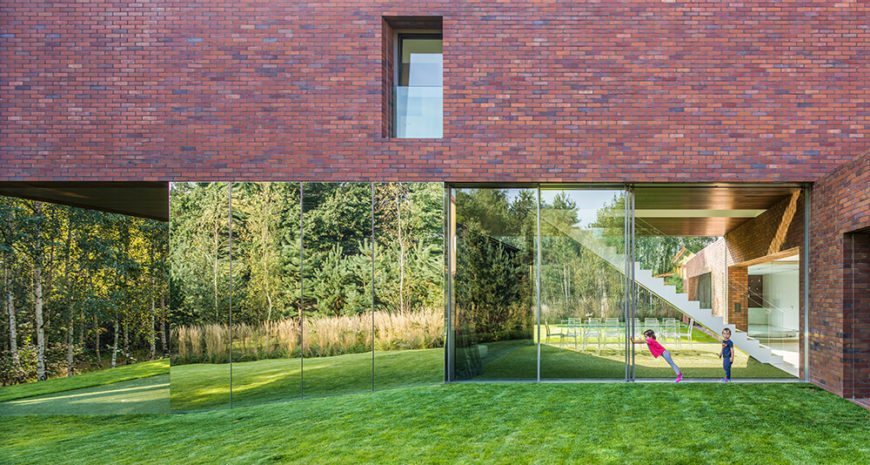 From the ground level, we can see the mirrored supports and glass partitions that serve as the only separation between the lower living areas and the backyard. To the left is a patio covered by the overhanging second floor.