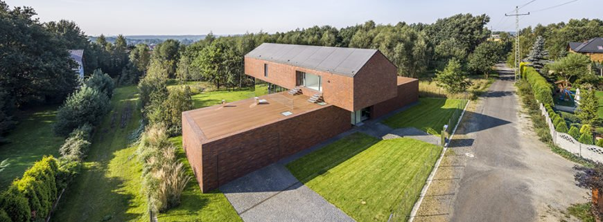An aerial view of the home shows the unique shape, where the top floor appears to extend far past the horizontal first floor. In reality, the top is supported by mirrored sides, which blend into the surrounding vegetation.