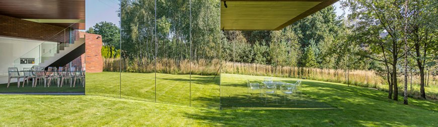 On the other side of the living room, outdoors, we can see a simple grass patio with translucent glass chairs and a table.