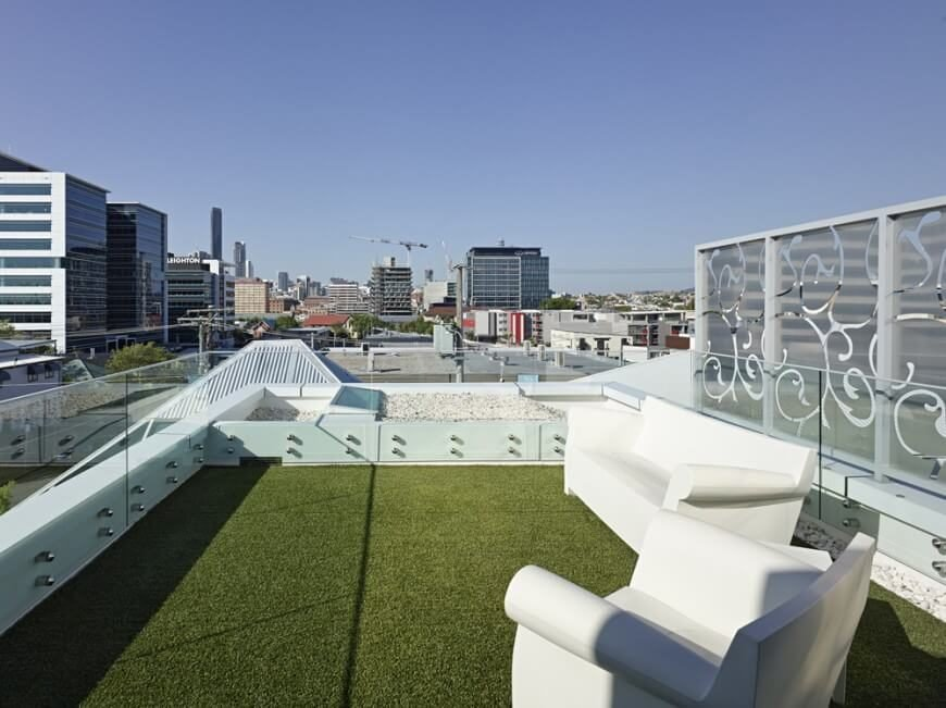 A beautiful modern urban rooftop patio with faux grass. The small patio is completely surrounded by waist-height glass balustrades and furnished with a white modern sofa and armchair. Frosted glass panels are visible beyond the balustrade to the right.