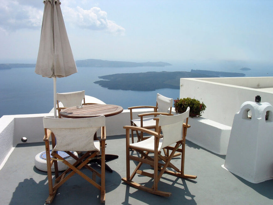 A small, private rooftop patio overlooking a beautiful, expansive view of a bay complete with an island at the center. The patio is furnished with a small table, umbrella, and rocking chairs.