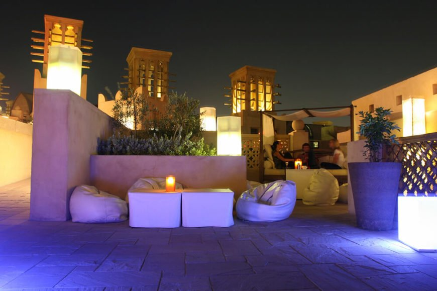 A rooftop patio at sunset illuminated by towers and lanterns. Aside from a pergola bench seating area are small bean bag chairs for lounging.