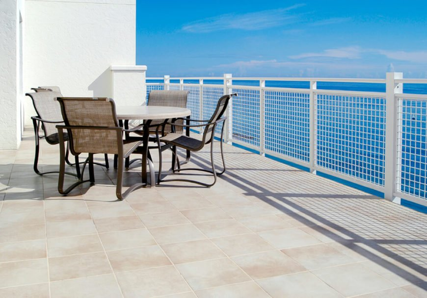 A contemporary rooftop terrace with a simple dining table and a fantastic view of the beautiful blue sea.