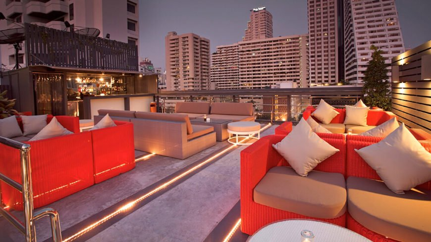 A large patio with rope lights built into the patio floor. Four intimate seating areas consist of beige or coral wicker furniture. The patio looks out over the city below.