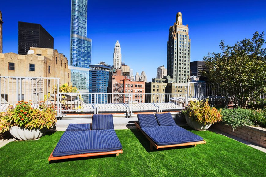 A lovely rooftop patio in the city with modular lounge beds and wrought iron fencing surrounding. Grass and large planting beds were added to give the spot a bit of shade and a more natural feeling.