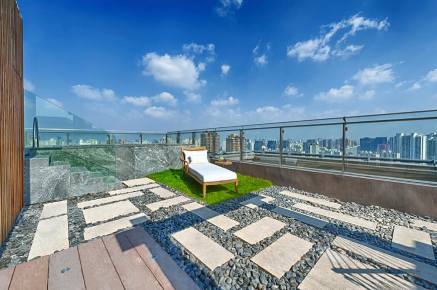 A larger rooftop patio will tall glass balustrades and stone steps. The patio is sectioned out into a wooden deck, a patch of sod, and pavers surrounded by stones, a design inspired by Japanese Zen gardens.