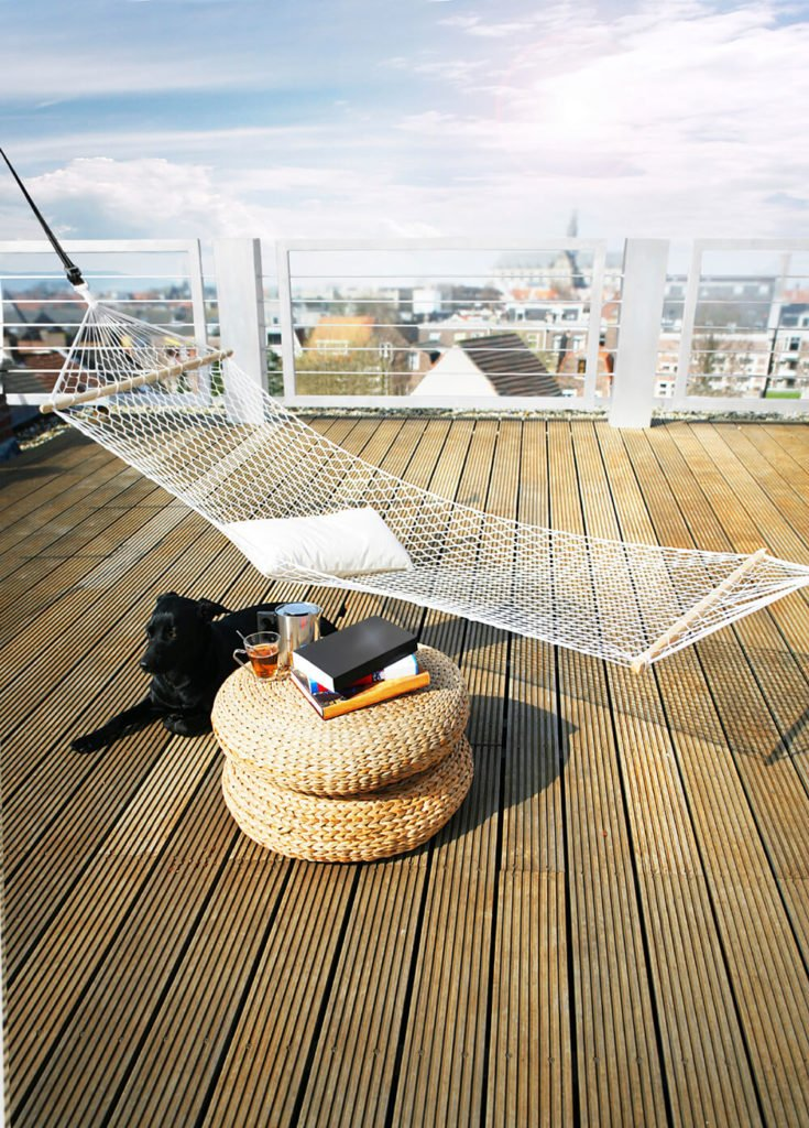 A private rooftop patio with textured plank decking, a wicker end table, and a single hammock.