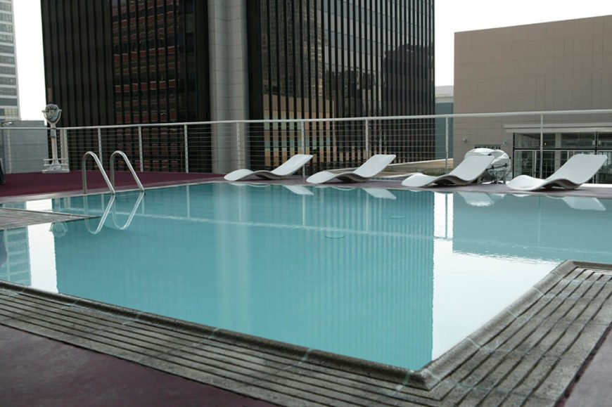 Surrounded by highrise buildings, this pool has a very modern look with the sleek lounge chairs around the far side of the pool. The burgundy patio offsets that pale blue color of the pool.