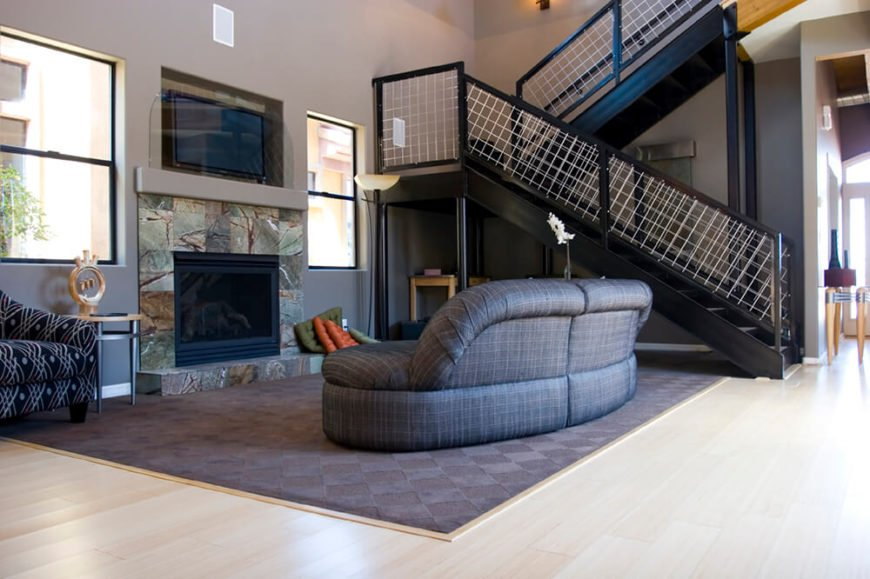 A modern living room is centered around a fireplace against the far wall. A television is securely nuzzled into a space above the fireplace where it can be easily accessed from the communal area.