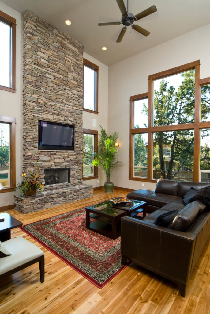 This massive fireplace suits the high ceilings in this room. The television has its own place between the stones where it can freely adjust to the liking of the occupants.