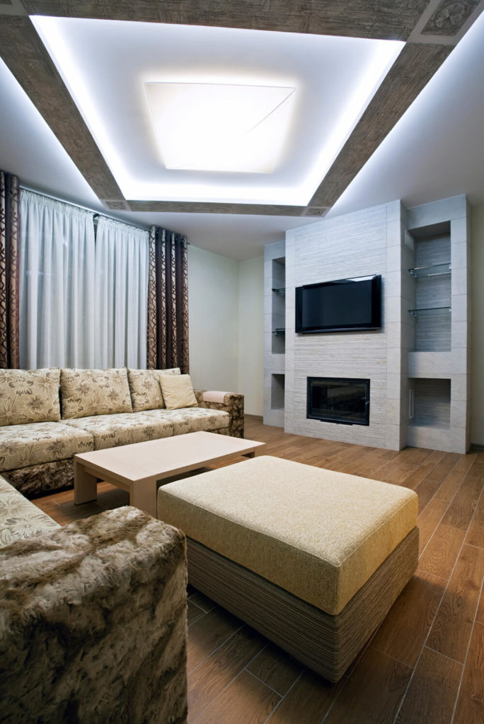 This living area has a minimalist setup for the fireplace. a seamless and white wall holds both the TV and the fireplace for a smooth appearance.