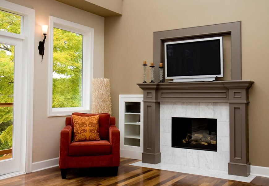 This fireplace has a large hearth made of gorgeous white marble. The mantle is a taupe wood that moves up to surround the television securely. The marble moves easily from the wall to the floor for a perfect combination of natural hardwood and white marble.