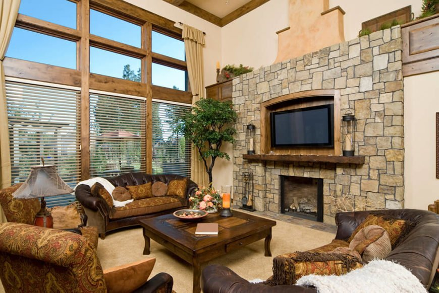 This country how has towering ceiling and a wide fireplace with plenty of gorgeous stonework. A television has its own nook built into the wall. The fireplace and TV are the same size for a symmetrical balance.