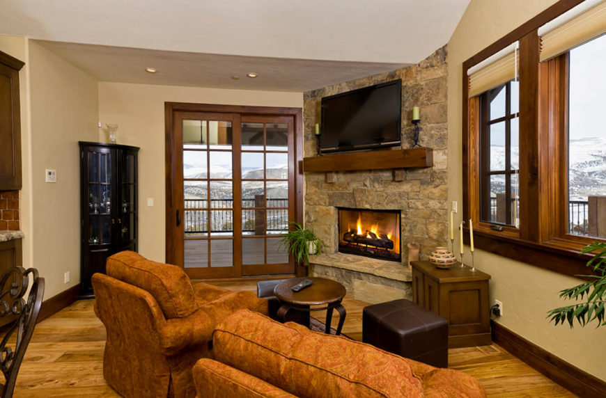 This country home uses a stone fireplace for a lavish touch in their quaint living room. The television is placed high enough on the stone fireplace to allow the natural fire to roar without clashing with the TV.