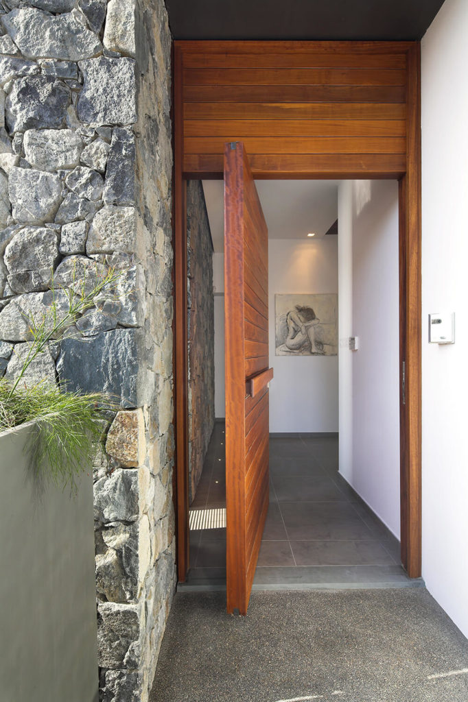 The large front door uses a thick slab of natural wood, giving way to a pristine white interior with grey large format tile flooring.