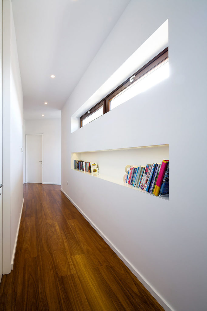 Moving down the hall to the more private areas of the home, we see a useful built-in bookshelf that mirrors the look of the window cutout above. The pristine white surroundings are anchored by the rich tone of natural hardwood flooring.