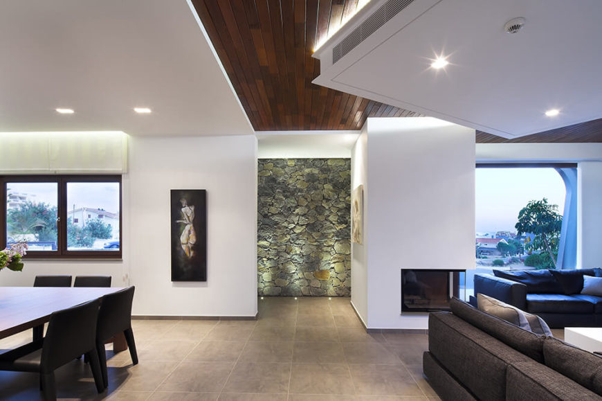 Seeing the broad open area at a glance, we can appreciate the mixture of elements, from large windows to stone walls to the rich wood ceiling panels, conspiring to bring about a complex but highly complementary palette.
