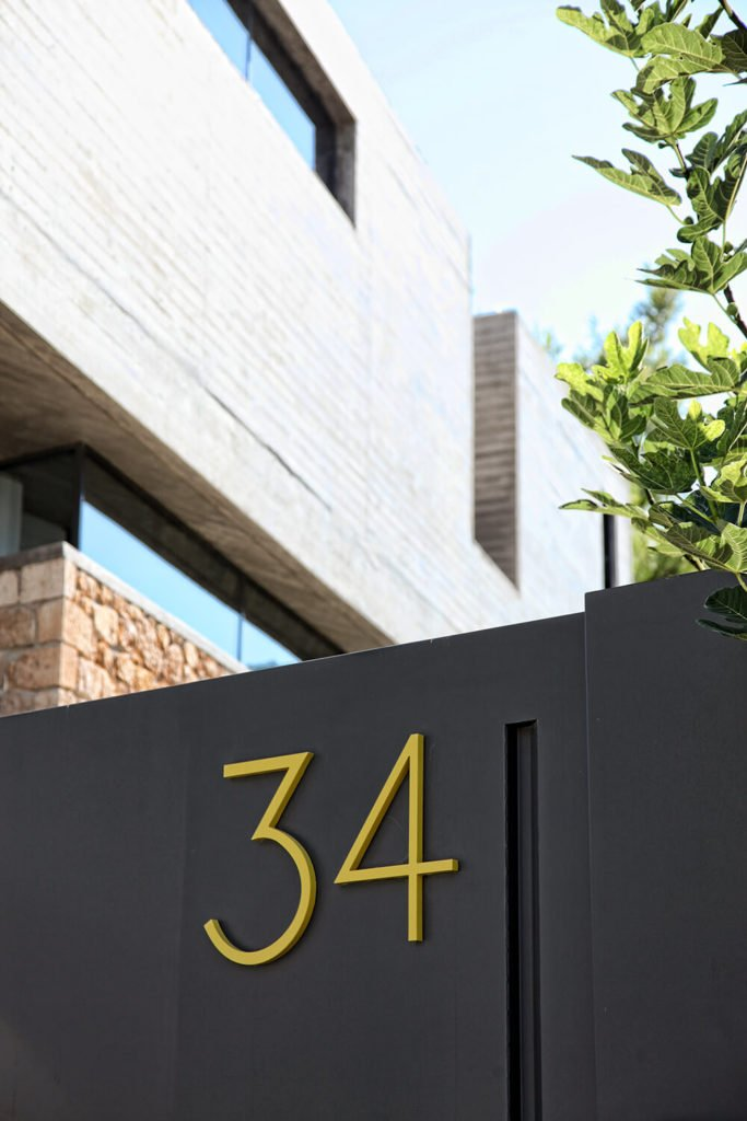 Bold yellow address numbers on the exterior of the house create a fun but structured look to the facade.