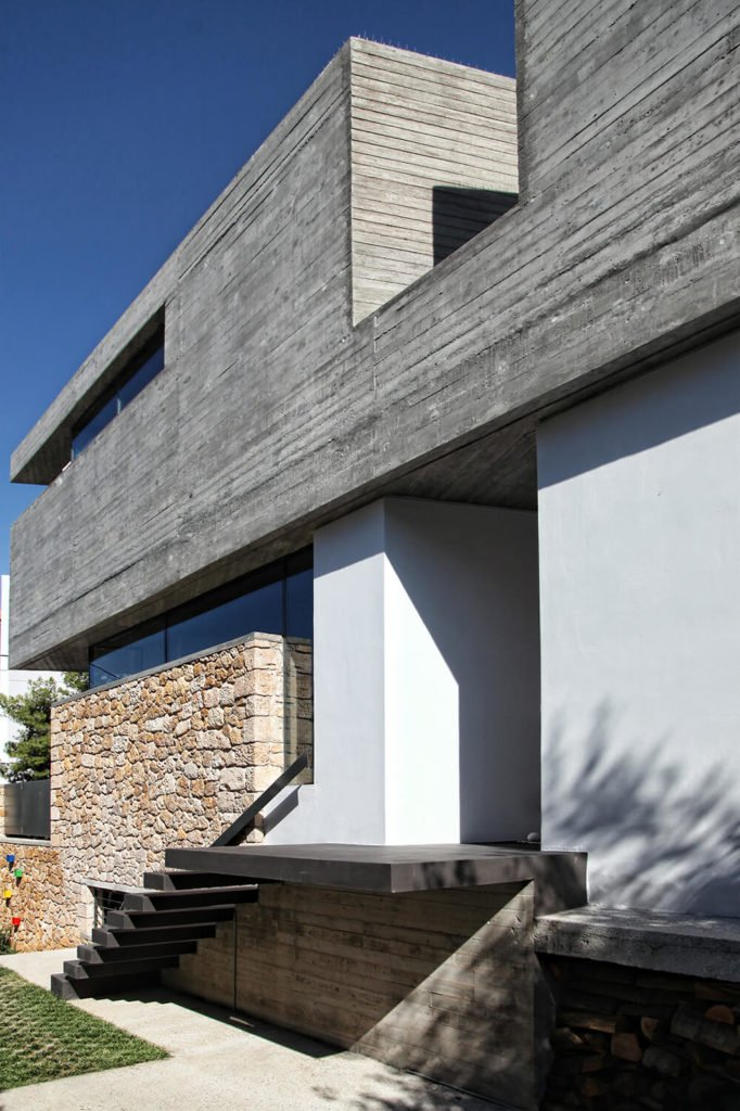 Here is a better view of the main entrance to the house with the floating stairs. The recession on the second floor is a visual mark for the front door but is also comprised of two walls of windows, ensuring that the second floor gets plenty of light.