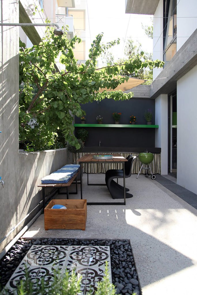Just outside the kitchen is the BBQ area of the open air courtyard. A small eating area and an outdoor prep area can be seen in the background. In the foreground it is small patch of patterned tiles surrounded by rocks that make up an outdoor shower for the pool.