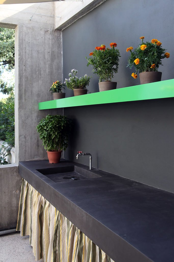 The outdoor sink and prep area continues the spring green theme from the kitchen utilizes the black material used around the exterior of the house. A prep sink that can also double as a garden sink and work area completes the counter.