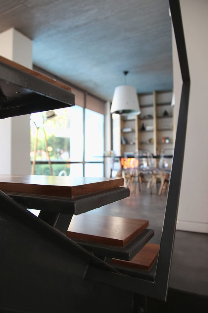 Here is a close up of the interior stairs and their steel and wood construction. The warm wood looks striking against the black of the steel supports. In the background you can see the dining area and the pool.