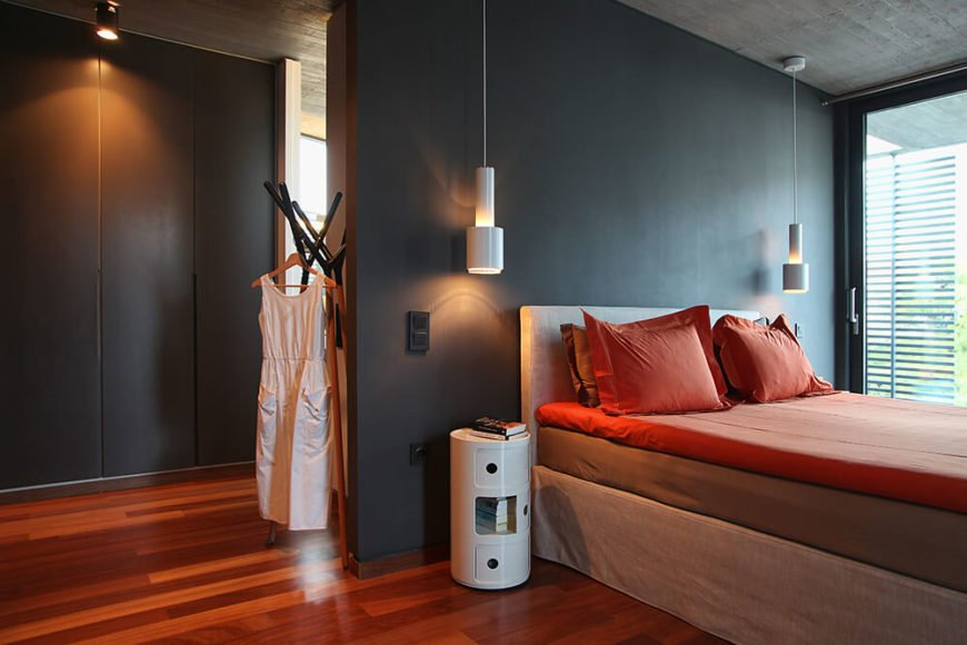 Pictured here in the primary bedroom of the second floor sleeping quarters. The wood floor from the living room is used throughout this floor and it complemented by the warm hues of the bed linens. Black walls and while accents allow this bright warm colors to pop.