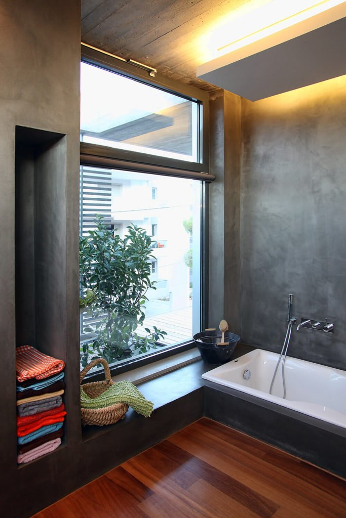 The attached bathroom to the primary suite looks out over the garden area of the balcony and offers privacy to the occupants. A bathtub and small bench a featured in this particular corner.