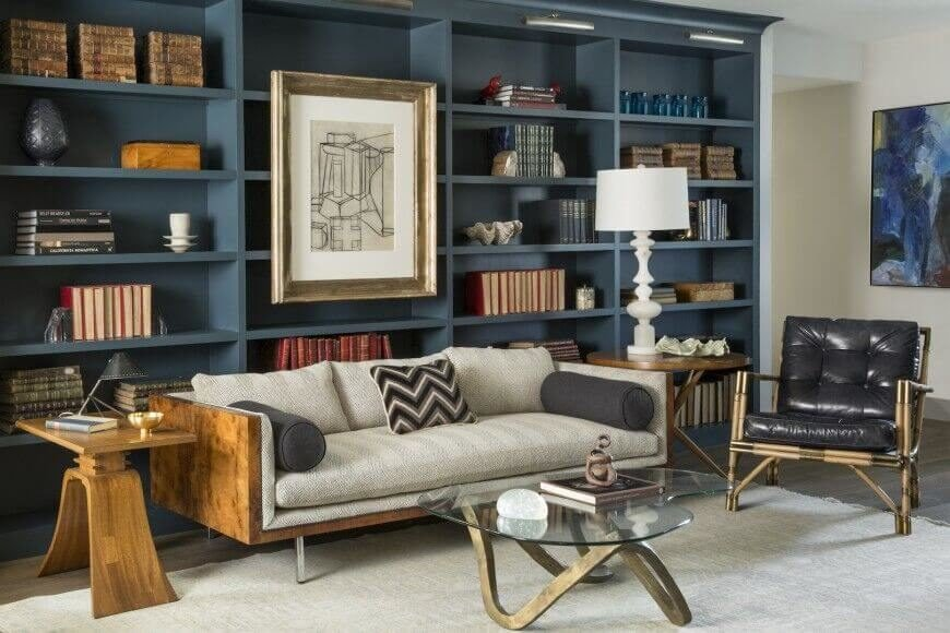 For owners with a smaller collection, arranging like items together with knick-knacks and accent pieces is a great way to fill the vertical space. This design also attaches a large piece of artwork to the empty shelves just above the sofa.