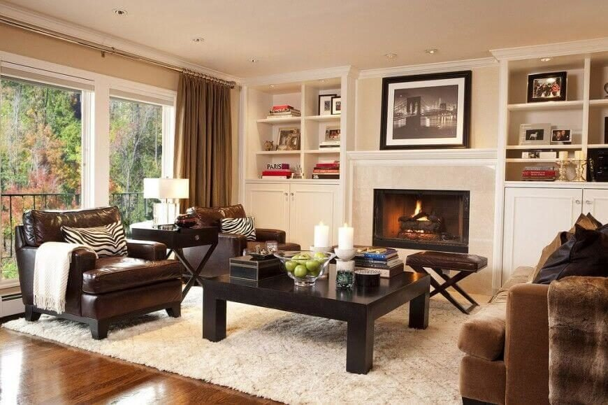The built-in shelves on either side of the fireplace are filled with books and family photos, with a photograph above the mantle as well.