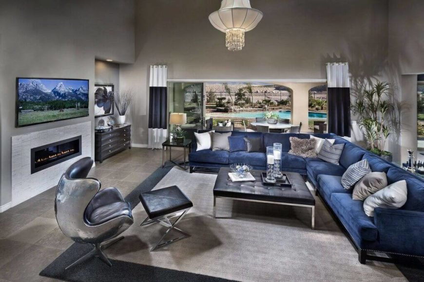 This metallic blue sofa might be in a cool color, but the sheer size makes it perfect for filling this enormous space. Note that the furniture is pushed away from the walls, and plants are used to fill open space between the back of the sofa and the wall.