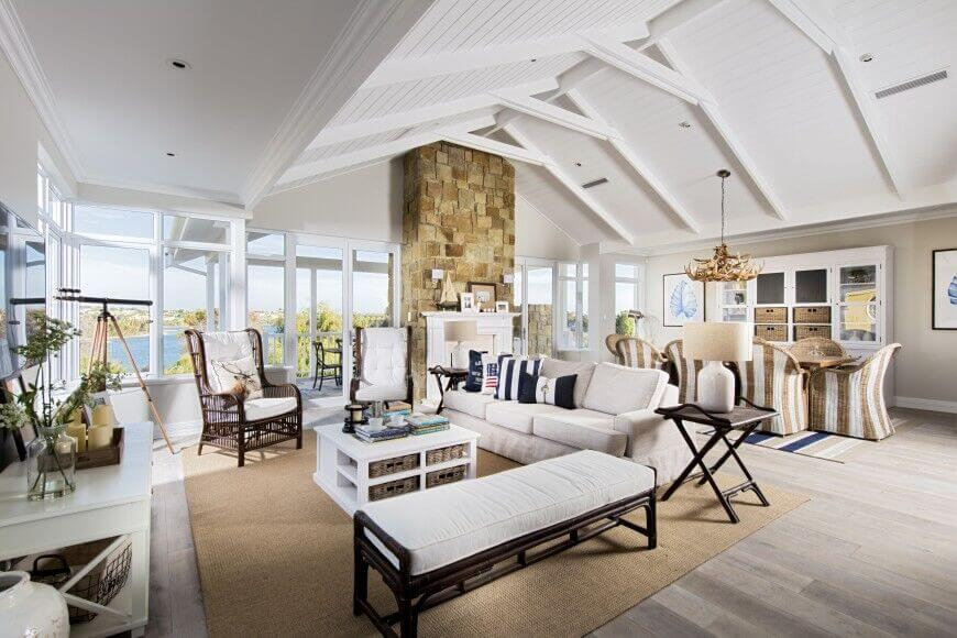 A soaring vaulted ceiling in white with exposed beams hangs above this vast open-plan living room. The exterior wall is entirely comprised of windows, for expansive views and natural lighting.