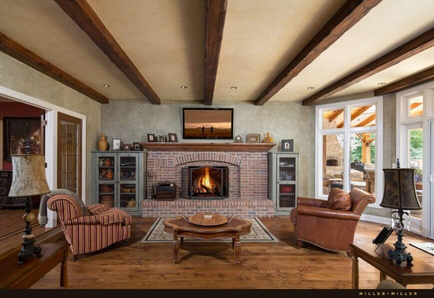 The large red brick fireplace is the centerpiece of this rustic living room. Natural hardwood flooring contrasts with beige walls and ceiling, crossed with exposed wood beams.