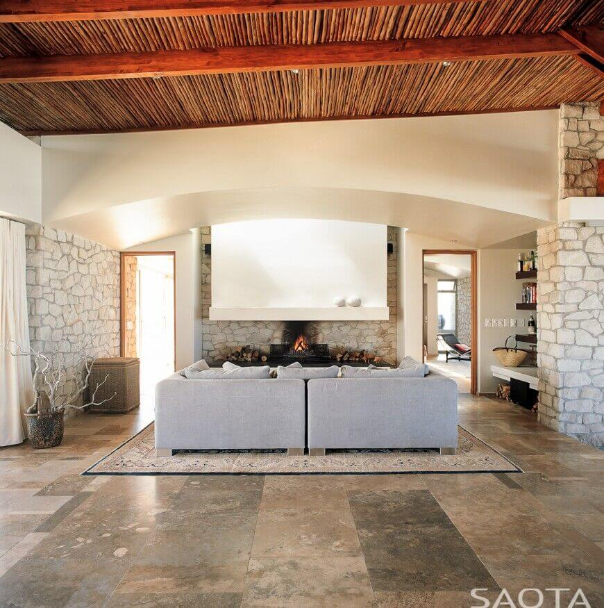 In a modern open plan home with stone walls and marble flooring, a natural wood vaulted ceiling with exposed beams brings the atmosphere down to earth.