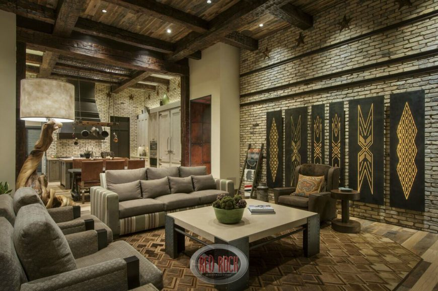 This deeply rustic living room sandwiches modern furniture between light brick walls. The double height ceiling sports dark rustic wood exposed beams for contrast.