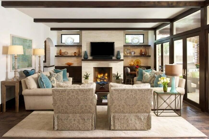 In a more cozy living room centered on light stone fireplace, dark exposed wood beams offer some contrast and complexity, matching the framing of the patio doors at right.
