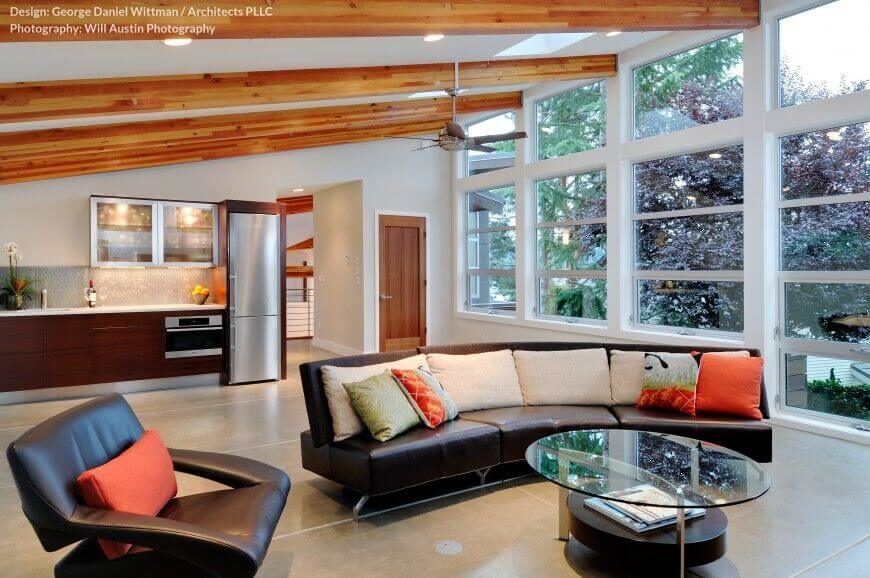 This minimalist open design living room crosses rich traditional materials with modern design. The sloped white ceiling is crossed with natural wood beams, glowing in the natural light courtesy of full height windows.