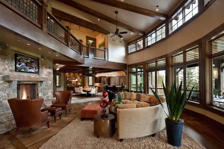 This expansive two story living room is surrounded by windows, highlighting the broad swaths of rich natural wood and stone. The white ceiling boasts the high contrast of dark natural wood exposed beams.