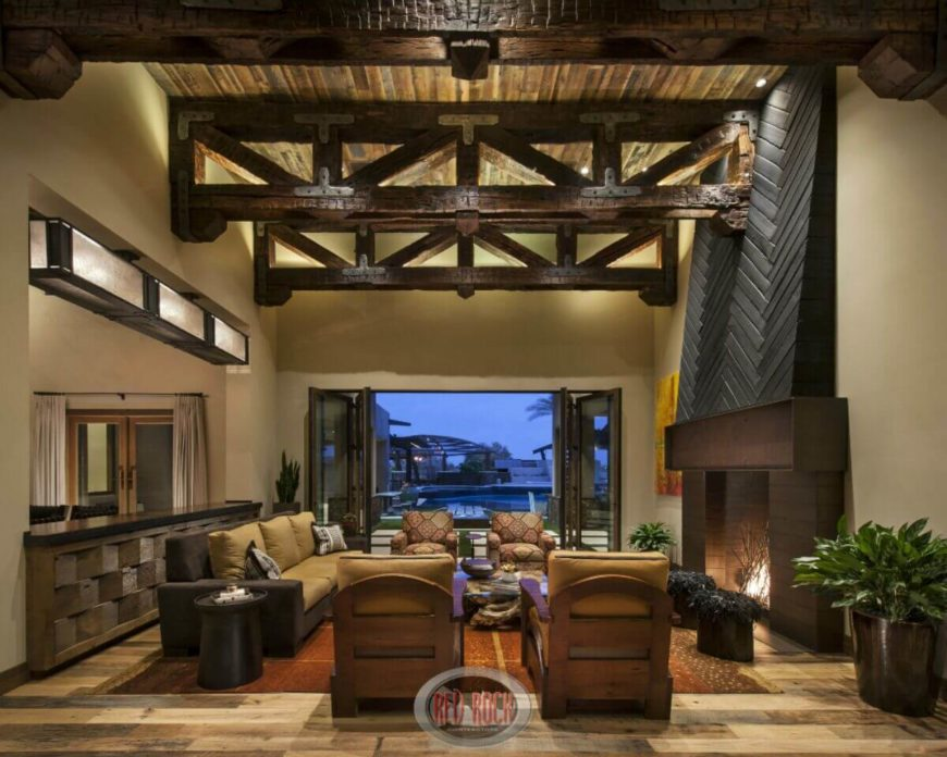 In a high contrast, modern rustic living room, burnt textured exposed beams fill in the upper area of the two-story room. Folding glass doors allow direct access to the patio.