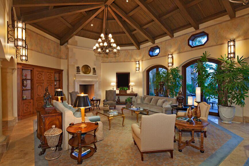 In a truly grand and elegant formal living room, a broad marble floored space sits beneath a massive vaulted ceiling in natural wood, crossed with exposed beams. A singular chandelier hangs from the center over a set of traditionally styled furniture.