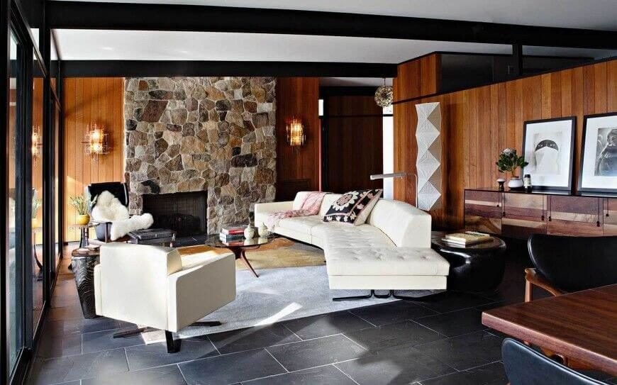 This contemporary setting pairs rich materials with a modern sense of scale. The stone fireplace wall, dark tile flooring, and rich wood walls share a space beneath a white ceiling with black painted exposed beams.