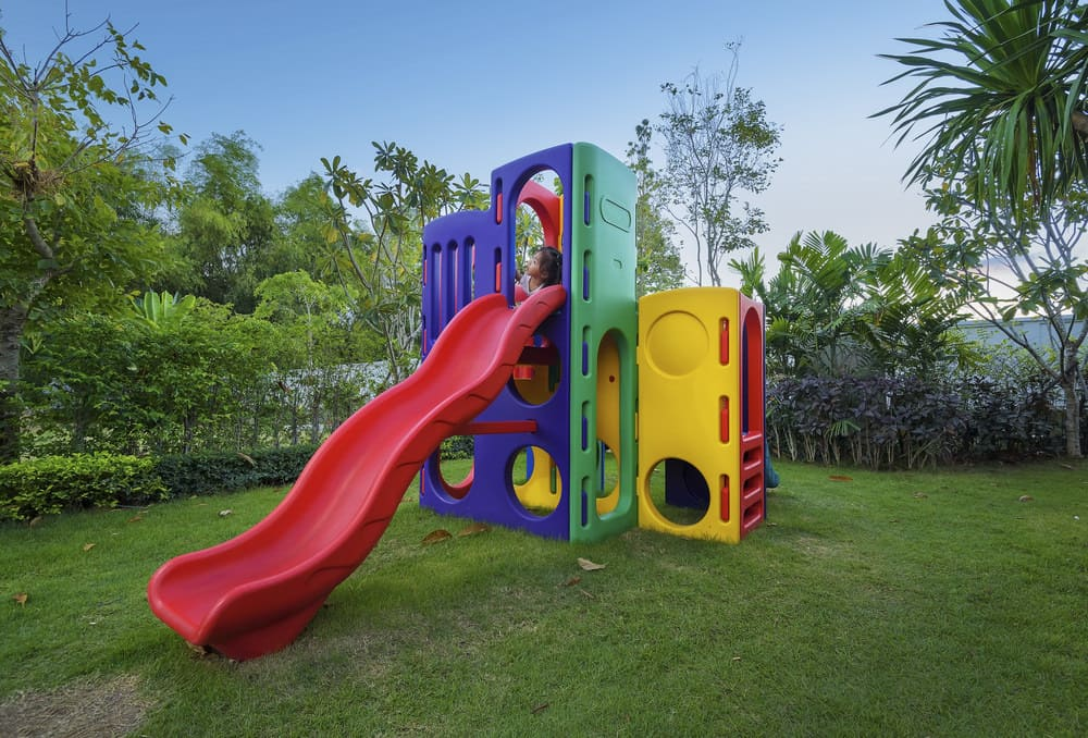 Colorful red, purple, green and yellow playground with tunnels and slide.
