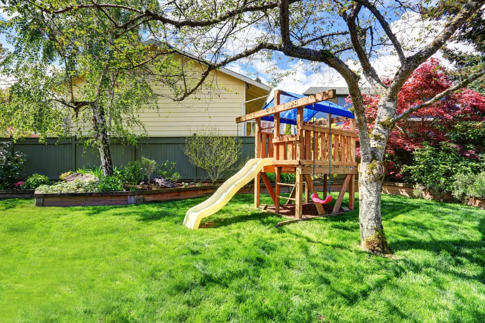 Small elevated playground platform with slide in the backyard.