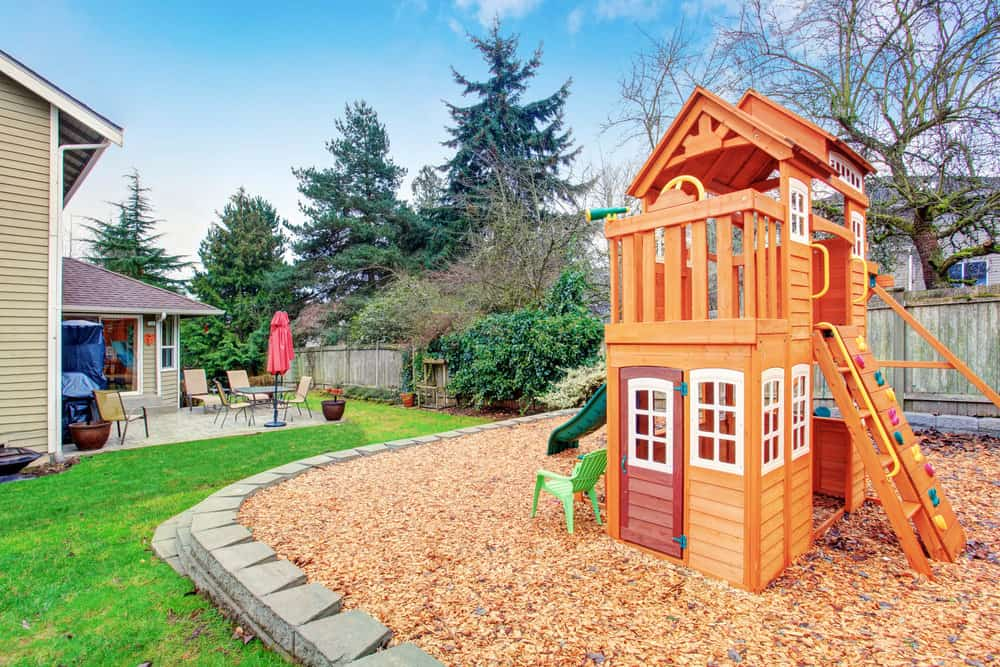 Small two-story playhouse with slide in large backyard.
