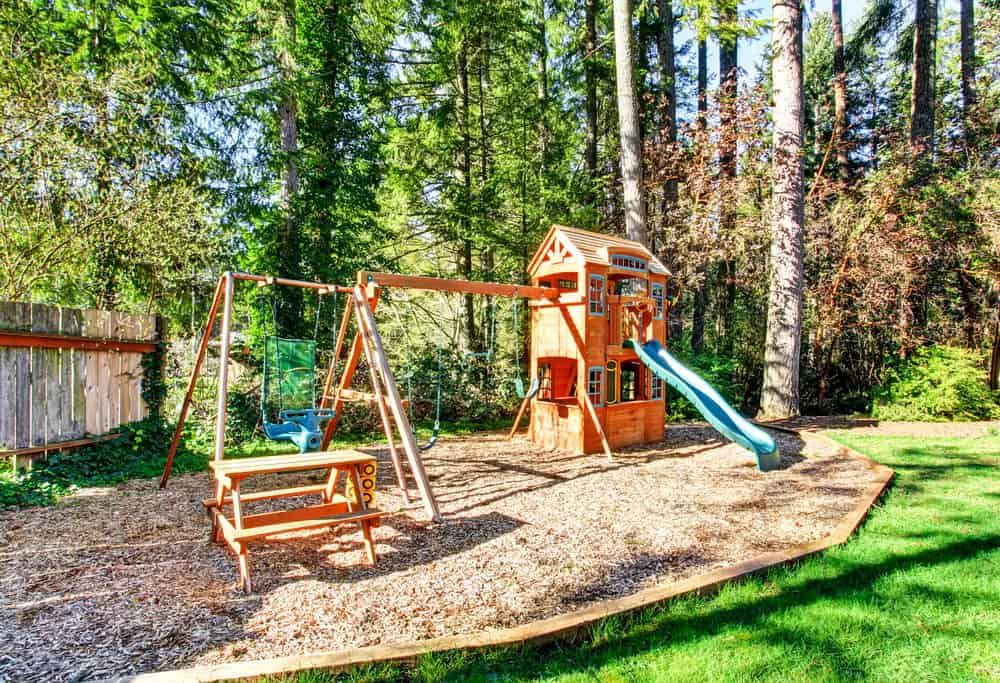 Great playground with 2 story fort, green slide, swing set and picnic table.