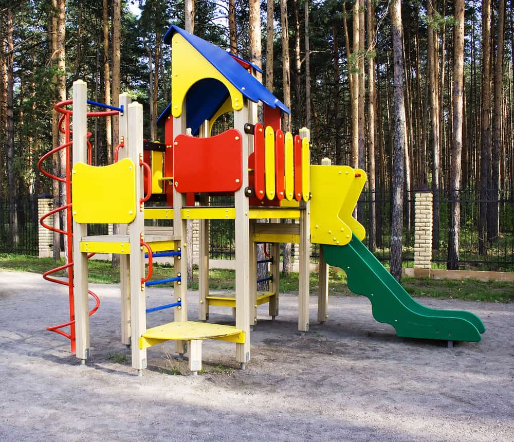Bright yellow playground for kids in the backyard with multiple levels, green slide and fort.