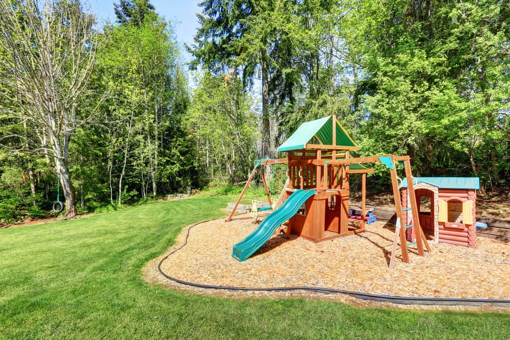 Extensive backyard playground on wood chip surface with green slide, swings and two playhouses.