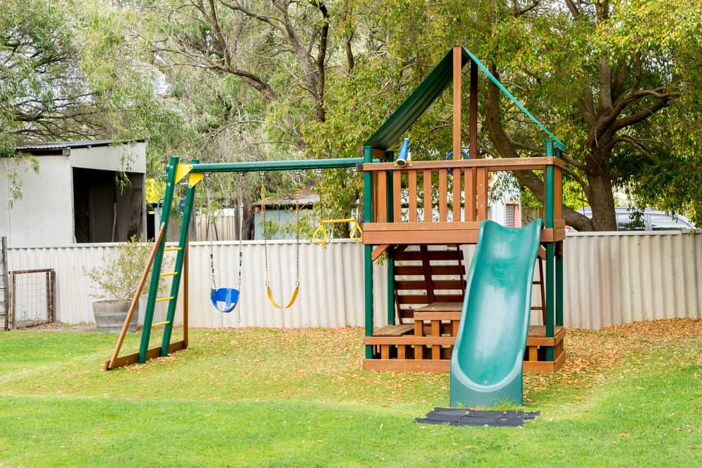 Large playground with large playhouse, swings (baby swing included) and green plastic slide.
