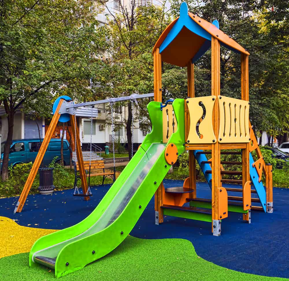 Colorful playground in backyard with gree slide, play fort and swing set on multi-colored turf.
