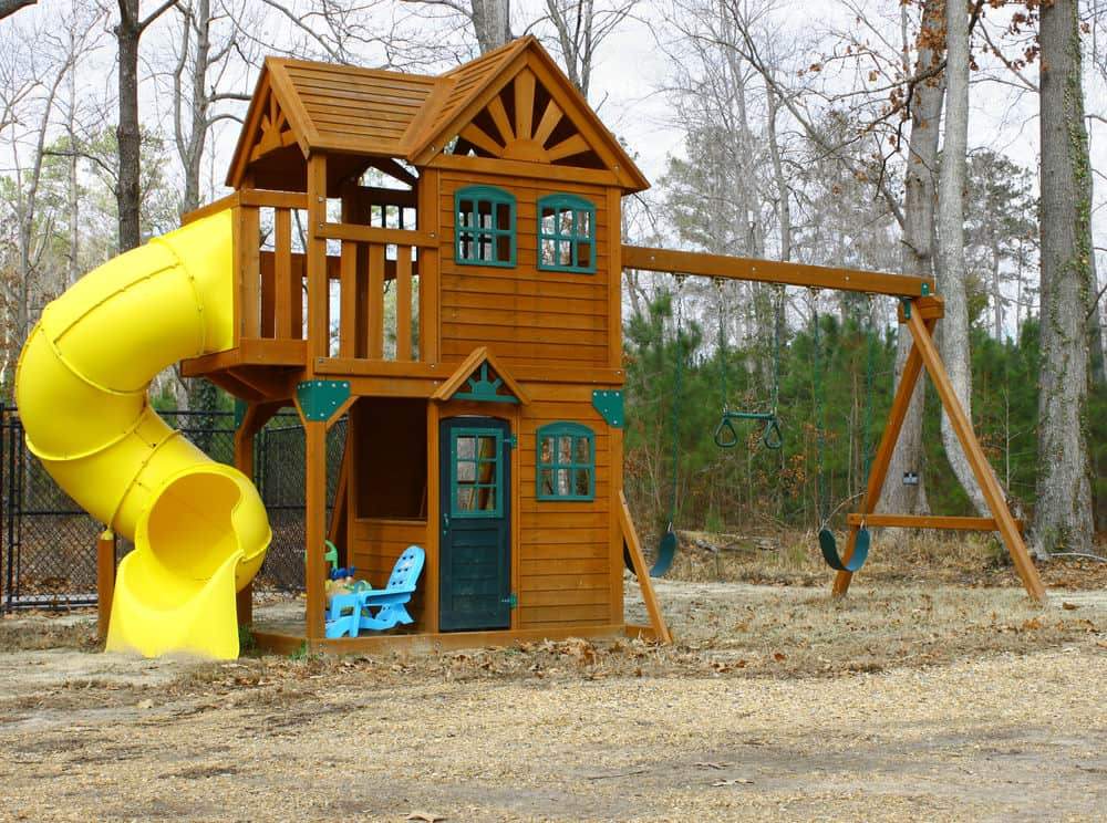 Large two-story play house with yellow tube slide and swing set.
